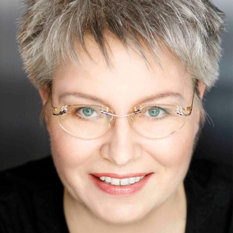 Freundlich lächelnde Dame mit dunkel und hellgrauer Igelfrisur; Brille, sehr helle grünblaue Augen und freundliches Lächeln; Sie trägt ein schwarzes Shirt mit großem Rundausschnitt.